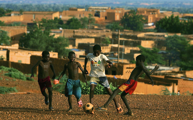 NIAMEY, NIGER - AUGUST 12: Nigerois boys play a game of soccer on August 12, 2005 Niamey, Nigeria. Niamey is the Capital of Niger. Niger is experiencing a food crisis which is threatening the lives of thousands in the impoverished West African nation. A combination of sever drought and a locust plague has caused the famine which has affected at least 2 million people in Niger and approximatly 5 million in the region. Niger is the second poorest country in the world, with 64 percent of the 12 millions inhabitants surviving on less than USD1 (81 euro cents) day. (Photo by Daniel Berehulak/Getty Images)
